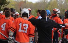 Lacrosse team huddle with Coach Gray and Coach Smith.