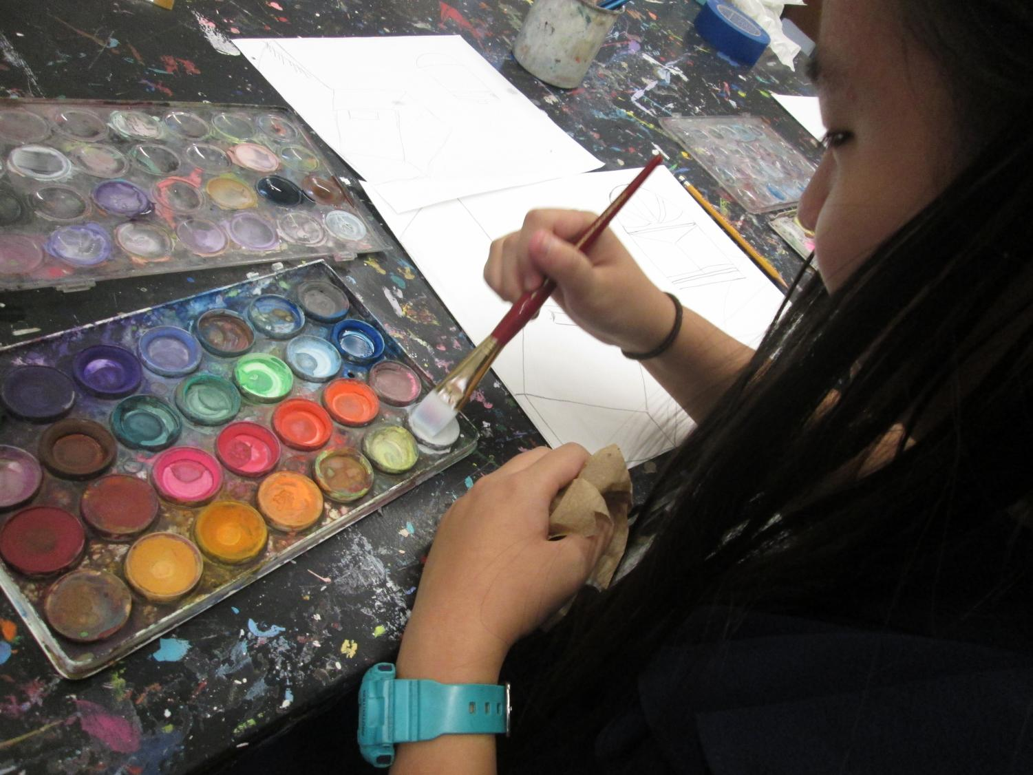A student in the Watercolor Painting elective chooses her colors. (Photo taken by a DiRectory student reporter.)