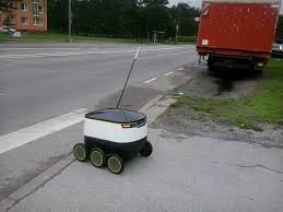 A Starship robot making its delivery to a college dormitory.