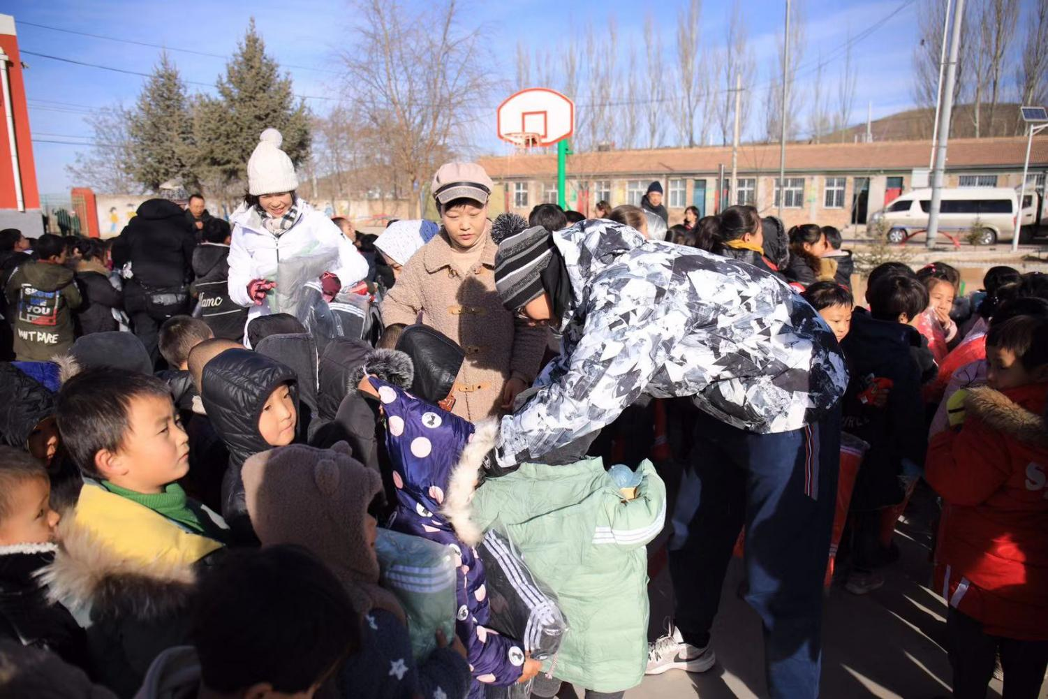 Antonio is passing out goods to the children in a school in Yinchuan, China.